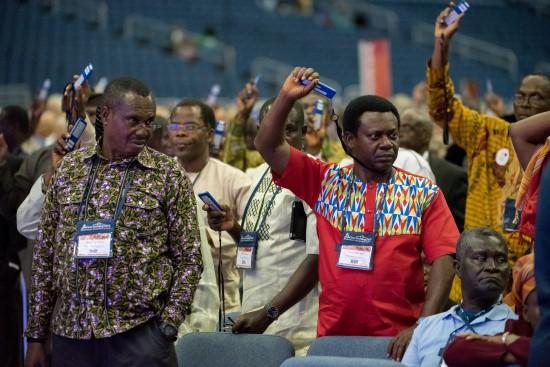 Delegierte halten Abstimmungsgeräte hoch